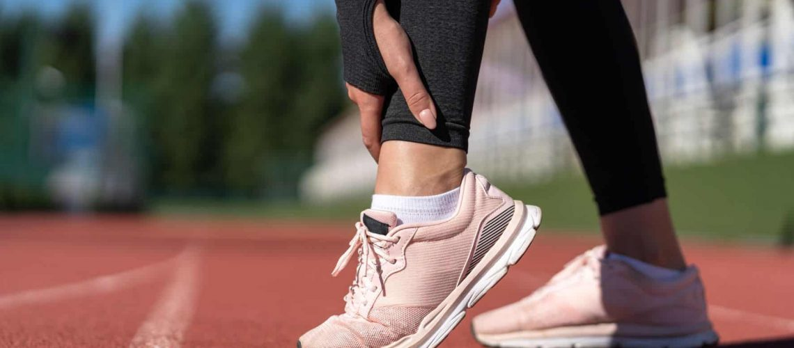 jogger-woman-runner-touching-foot-in-pain-due-to-s-9XWDALR