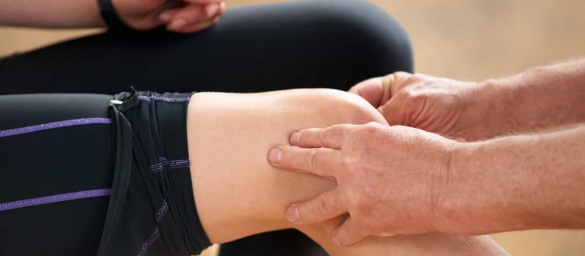 Young woman having leg injury. Close up male hands massaging leg of an injured woman at the gym. Sport injury concept.